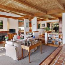 Open Living Area With Fireplace, Custom Beams And Built In Storage